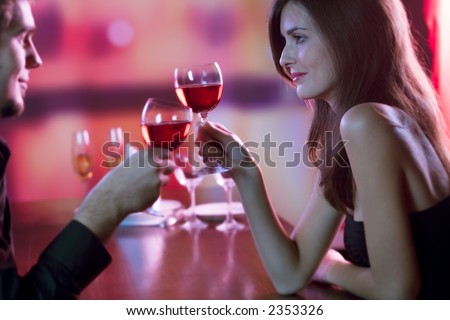 Young couple sharing a glass of red wine in restaurant, celebrating or on romantic date. Focus on woman. - stock photo