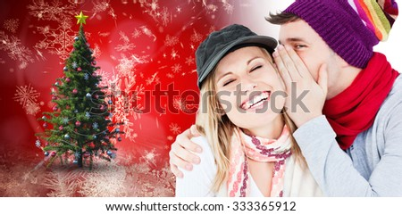 Young couple sharing a secret against christmas tree - stock photo