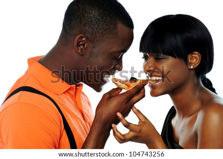 Young couple sharing a slice of pizza isolated over white background - stock photo
