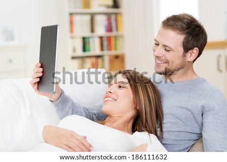 Young couple sharing a tablet computer as they relax together on a sofa with the wife reclining on her husbands chest - stock photo
