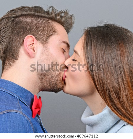 Young couple sharing romance and kissing against gray background - stock photo