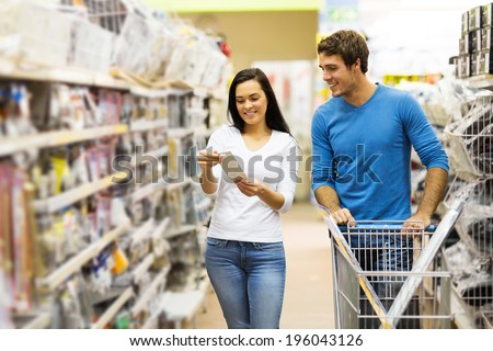 young couple shopping for DIY tools at hardware store - stock photo