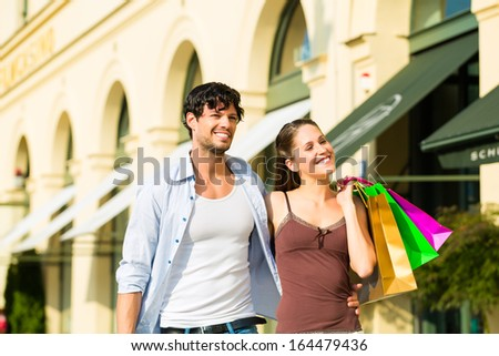 Young couple shopping in inner with shopping bags spending money - stock photo