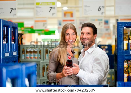 Young couple shopping together at supermarket and looking for groceries