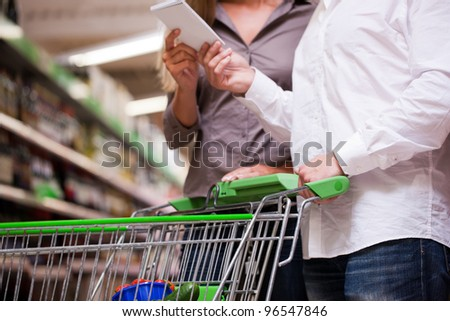 Young couple shopping together with trolley at supermarket