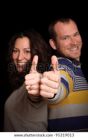 young couple showing thumbs up in front of black background - stock photo