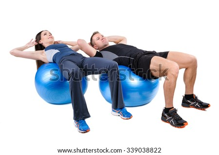 Young couple shows starting position of Abdominal Fitball Workout, isolated on white - stock photo
