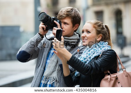 Young couple sightseeing and taking pictures on the camera and a smartphone