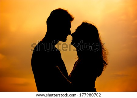 Young couple silhouette, dating, orange background