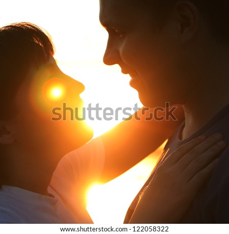 Young couple silhouette hugging and looking at each other outdoors at night neon city background