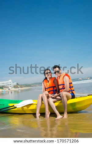 Young couple sin canoe looking at camera - stock photo