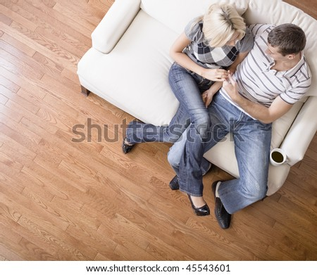 Young couple sit on a cream colored love seat and gaze into one another's eyes. Horizontal shot
