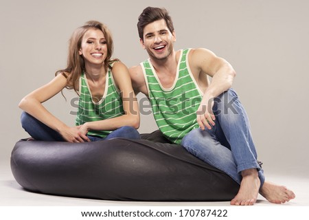 Young couple sitting and relaxing on black sofa  - stock photo