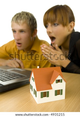 Young couple sitting at desk in front of computer. They are looking surprised. House miniature is standing on desk. Focus on little house. White background, side view - stock photo