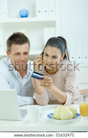 Young couple sitting at desk shopping on internet from home. Calling phone, using laptopcomputer and paying with credit card. - stock photo