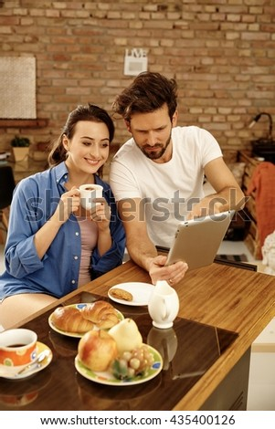 Young couple sitting at morning table, using tablet computer, having breakfast. - stock photo