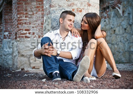 Young couple sitting by brick wall - stock photo