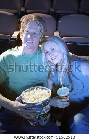 Young Couple sitting close, lying on shoulder Watching Movie Together in theatre - stock photo
