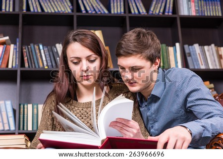 Young couple sitting close together paging through a large red book in the library as they search for information
