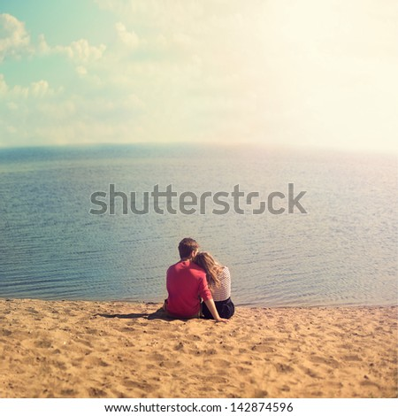 young couple sitting embracing on the sand looking out to sea - stock photo