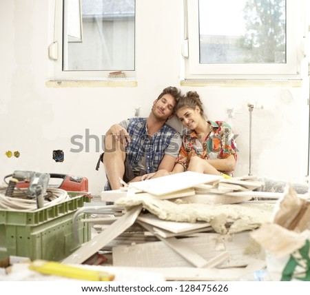 Young couple sitting exhausted in house under construction among construction waste, smiling. - stock photo