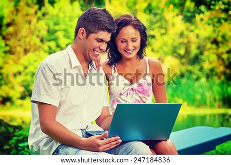 young couple sitting holding laptop looking on it and smiling instagram stile