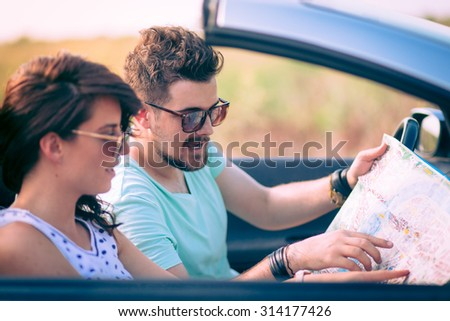 Young couple sitting in cabriolet and looking at the map - stock photo