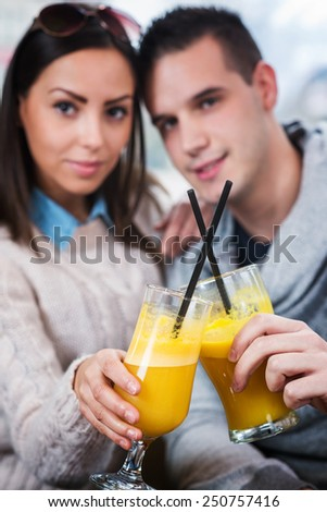 Young couple sitting in cafe and toasting with glasses of orange juice. - stock photo