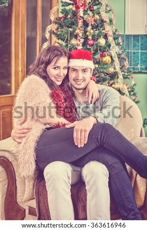 Young Couple Sitting in Chair in Their Home in Festive New Year's and Christmas Atmosphere. Behind Them Is Christmas Tree with Ornaments. Love and Affection in the Warm Ambience. Holidays - stock photo
