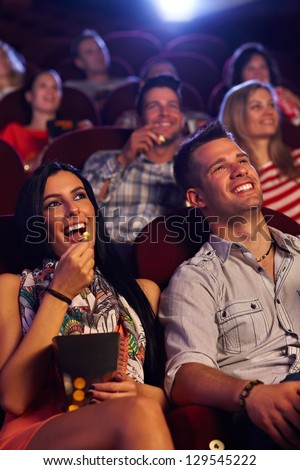 Young couple sitting in cinema, watching movie, eating popcorn, smiling. - stock photo