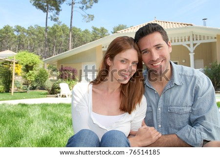 Young couple sitting in front of their new house