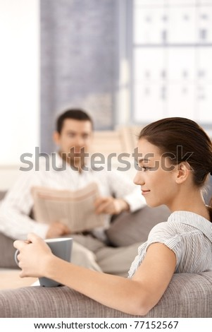 Young couple sitting in living room on sofa, man reading newspaper, woman drinking tea, smiling in front.? - stock photo