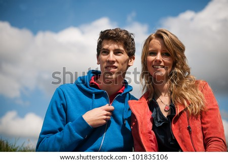 Young couple sitting in nature grass landscape - stock photo