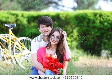 Young couple sitting in park with bicycles