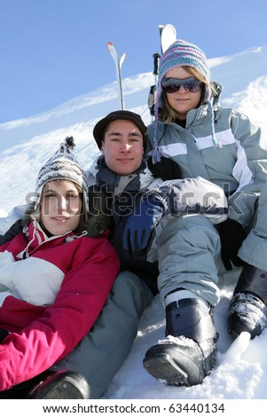 Young couple sitting in snow - stock photo