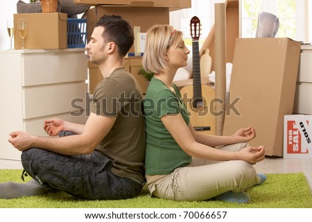 Young couple sitting in yoga meditation posture on carpet in new house, surrounded with boxes.? - stock photo