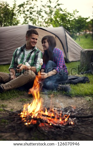 Young couple sitting near a campfire and toasting marshmallow - stock photo
