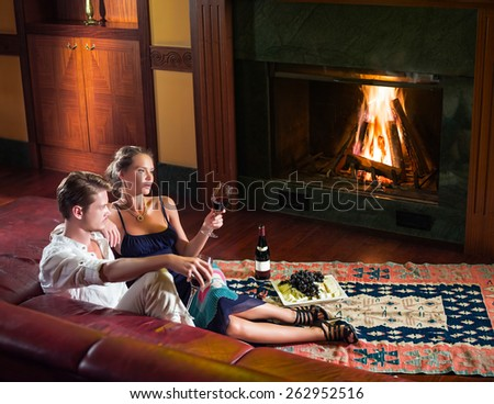 Young couple sitting near the fireplace  - stock photo
