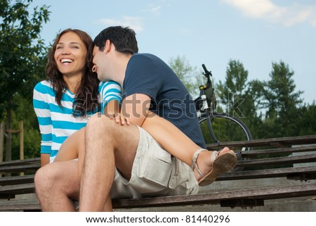 Young couple sitting on a bench - stock photo