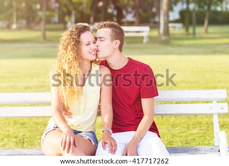 Young couple sitting on a bench, enjoying in the park on a sunny  summer day - stock photo