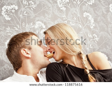 young couple sitting on a couch together a cookie bite her lips - stock photo