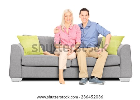 Young couple sitting on a modern sofa isolated on white background - stock photo