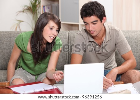 Young couple sitting on a sofa with a laptop - stock photo
