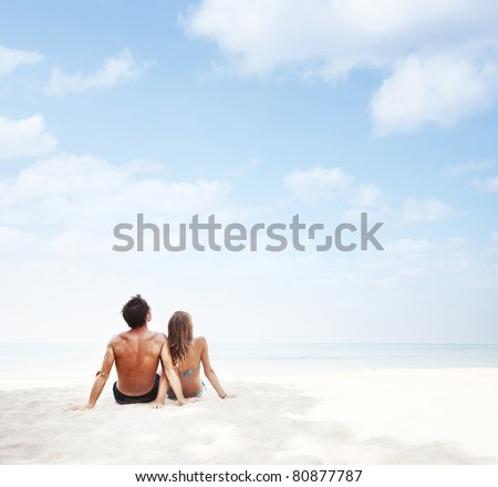 Young couple sitting on a white beach and looking to a blue cloudy sky - stock photo