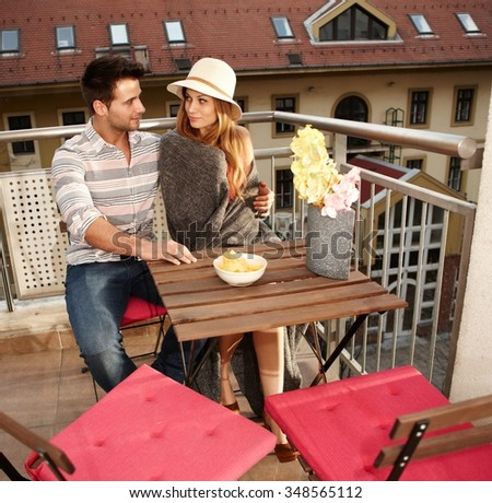 Young couple sitting on balcony, embracing, smiling. - stock photo