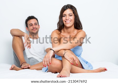 Young couple sitting on bed in bedroom. - stock photo