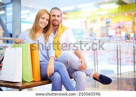 Young couple sitting on bench in shopping mall - stock photo
