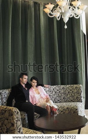 Young couple sitting on couch with martini glass on coffee table in hotel lobby - stock photo