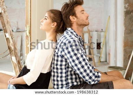 Young couple sitting on floor exhausted in renewing house. Sitting back to back. - stock photo