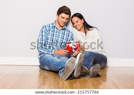 Young couple sitting on floor with gift at home - stock photo
